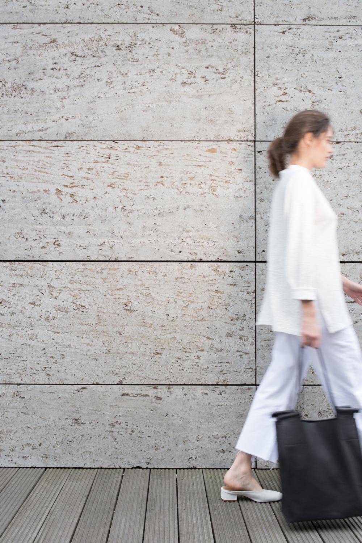 Eine Frau mit Handtasche läuft aus dem Bild.