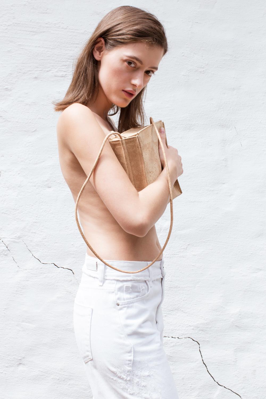 Eine Frau bedeckt ihre Brust mit einer Handtasche aus Kork-Leder. Sie trägt eine weiße Hose und guckt sexy in die Kamera
